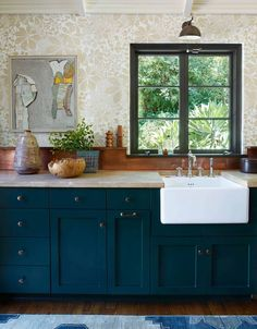 The kitchen wallpaper, by Marthe Armitage, the ceramics by Kevin Willis, and the earthy stone counters echo the organic, leafy presence of the garden outside.