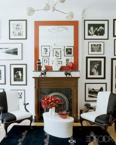 In the sitting room, black-and-white armchairs from Ralph Lauren Home and framed photographs make a bold statement when paired with a large red-framed mirror. The lacquer table is by Robert Kuo and the Eileen Gray rug is from Ralph Pucci International.