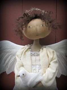"Hope is an one-of-a-kind angel. She measures 19"" tall and wears antique clothing. Her face is hand painted and stitched and her hair is soft brown mohair. She has a halo made from antique tinsel and she carries a tiny dove that I made from felted wool. Her wings are real feather wings.  Many thanks for stopping by!"