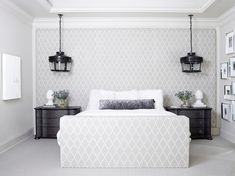 Chic bedroom features a gray lattice fabric paneled wall doubling as headboard is lined with a queen bed and matching footboard dressed in white sheepskin pillows and a dark gray crushed velvet lumbar pillow flanked by suspended glass pendants illuminating dark wood nightstands.