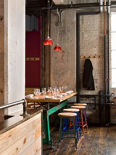 Coloured accents and coloured glass lighting lift this industrial space to be a fun and more feminine space.