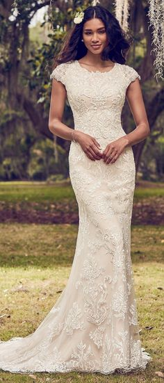 Maggie Sottero - DAISHA, This modest sheath wedding dress features allover lace motifs atop tulle, with embellished lace motifs and Swarovski crystals along the cap-sleeves.