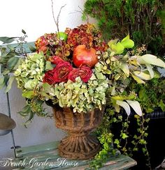pomegranates, roses and hydrangeas in an antique urn