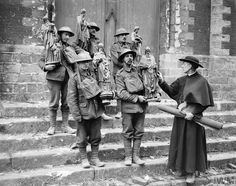 WWI, 26 Feb 1918; British soldiers helping Father Leon Peulmeule, the temporary curate of Armentieres, to remove statues and relics from the Church of Saint Vaast which has been damaged by shell fire. Armentieres. © IWM (Q 8544)