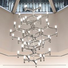 An eccentric, modern twist on classic chandelier design. The Nemo Crown Summa Chandelier features a stunning, die-cast aluminum body that consists of many tripodic lines and illusory hexagonal patterns that shift depending on your point of view. Dotting the end of each line is one of 48 sandblasted, opal-white glass diffusers that, in concert, elicit a widespread, yet warm lighting effect. Includes field-cuttable transparent cables for discreet suspension.