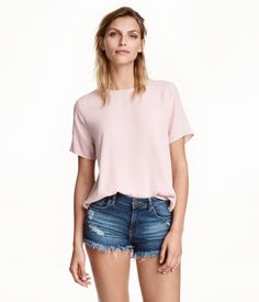 Light pink. Straight-cut blouse in crêped woven fabric. Opening at back of neck with pearlescent button, short sleeves, and rounded hem. Slightly longer at
