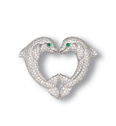 A DIAMOND AND EMERALD DOLPHIN CLIP BROOCH, BY CARTIER Of heart-shaped outline, designed as two pavé-set diamond dolphins with emerald eyes, mounted in 18k white gold, 5 cm wide, with French assay marks for gold and maker's mark Signed Cartier, no. 723237
