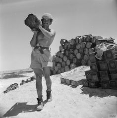A South African sapper carrying a stack of mines, Egypt, 2 July 1942.