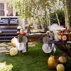 "Set the scene for a spooky soiree in your own backyard. Paper decorations (including paper fans and a banner spelling ""potions""), grab-and-go food, and painted pumpkins propped against thrifty tables is all you need for a wonderful welcome./"