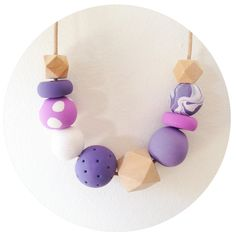 Individually handmade (hand rolled and blended) polymer clay beads, with wooden beads. Round leather cord. Two slip knots for adjustable length