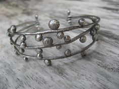 Sterling silver organic twig cuff bracelet. Three strands of fabricated twigs are joined together with a pin so that this cuff has a bit of