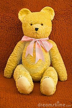 Cute old teddy bear on red background