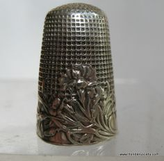 Silver thimble, French cir 1890. An Art Nouveau design of a flower in fine relief, with foliage curling all the way around the border. #sewing #thimble