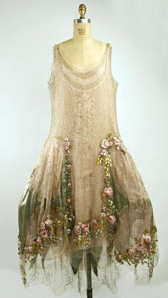Boue Soeurs Evening Dress c. 1923 - 1925. The Boué sisters had one of the most recognizable styles in fashion. They were renowned for their romantic designs which often borrowed details from historical paintings.  The Boué sisters made great use of light-refracting silver and gold cloth. Another house signature was floral patterned lace. Embroidery was done in Venice on sheer organdie. Dhoop-chaon taffeta was also used to make different hues shine at different times.