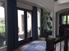 Draperies are two finger pleated functional panels. They can cover the entire wall for protection from the east sun. When they are open they really complete the look of the entry way.   Design by Traditions Window Decor Dallas