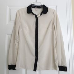 Merona cream and black button down blouse Loving this with a blazer or tucked into a black pencil skirt! Semi sheer. 100% polyester. EUC. 26 inches long. Merona Tops Button Down Shirts