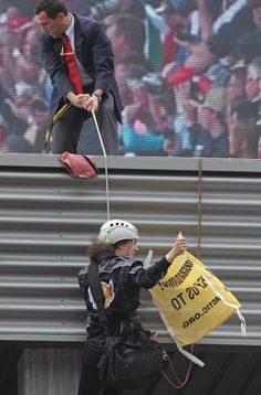 A security officer tries to pull up a Greenpeace activist during the podium ceremony of the Belgian Formula One Grand Prix in Spa-Francorchamps, Belgium after the 2013 F1 GP