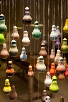 Red, you light up my life! Painted light bulbs hanging from fishing wire makes activates the space in a window display.