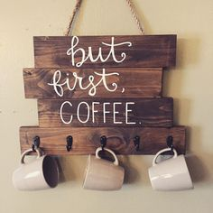 Wood coffee sign with But first, Coffee hand written. Five hooks are attached at the bottom to hang coffee mugs, and sign is hung by rope.