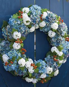 Show your patriotic spirit in a more subtle and elegant way. Our all-season Americana Wreath brims with bouquets of Blue mophead hydrangeas, clusters of white Annabelle hydrangeas, and wild red raspberries.