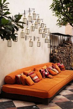 Daybed with a plethora of cushions & overhead lanterns