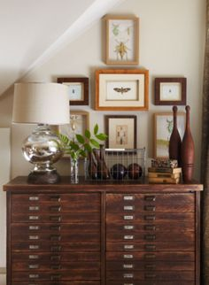 Lovely vignette of old game pieces and framed insects above an antique printer's cabinet with brass pulls. (Photo: Jean Allsopp Photography)