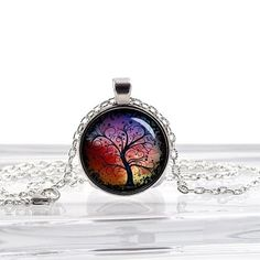 Due to overwhelming demand for our products and the customization required, we can not guarantee orders made after December 18th will be delivered by Christmas. We'll try our best, but we can't guarantee it.Tree of Life Red and Blue Beautiful Glass Photo Pendant Silver Necklace Jewelry Includes chain! (Watermark copyright text will NOT appear on Actual Pendant) Image is Enlarged to show detail. This Charm is 1 Inch in size. This Pendant has Beautiful Artwork sealed under Glass so its m...