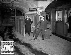 Employé du métro retenant le portillon automatique pour laisser passer un voyageur à Paris, en janvier 1947. Sur le mur, en haut à droite : un avis en anglais subsistant de l'époque de la Libération.