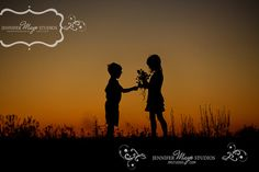 children picking wildflowers silhouette at sunset on Grenadier Island in the Thousand Islands region near Cape Vincent, New York on Lake Ontario