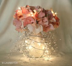 Pretty reception centerpiece - made with silk flowers, an ice-drop garland, white LED lights, a glass vase, and shredded cellophane filler.