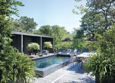 Hamptons Cottages & Gardens  Black Beauty photographs by Peter Murdock  Housemates Rob Southern and Bill Melnick added a new pool and wraparound bench. The outdoor furniture is from Restoration Hardware; the umbrellas are from Thayer's Hardware & Patio in Bridgehampton.
