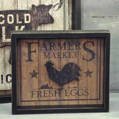 """The warmth and honesty of American farmhouse style is the perfect setting for this Fresh Eggs Sign. This vintage inspired open shadow box sign will look great in a country kitchen or farmhouse keeping room. A distressed black frame surrounds the painted sign that features a rooster silloutte projected 1/2"""" from the back. 11.75""""W x 10""""H x 1.75""""D"""
