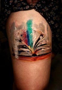 This colorful Art of book tattoo. Array of colors coming out of the real- time book tattoo is worth considering, if you are a literary kind of a person.