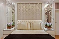 Cabeceira capitonê pequena, com espelhos laterais, papel de parede neutro, iluminação de spots e pendentes de cristal