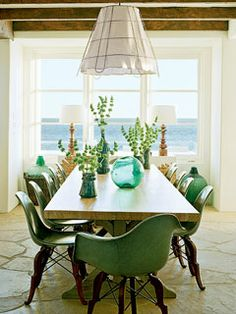 This 13-foot-long tabletop is made of wood from an old bowling lane. It seats 12 classic Eames fiberglass shells on wire-and-walnut bases. Sea green and natural wood textures unite the space with the stone floor and exposed-beam ceilings. A wire-basket chandelier lined with linen is the perfect informal touch and completes the look in this Malibu Beach, California, dining room. myhomeideas.com