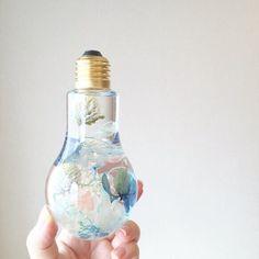 【爽やかブルーのフラワーバルブハーバリウム】ドライフラワーやプリザーブドフラワーをミックスした爽やかなブルーのフラワーバルブボトルハーバリウム* 人気の電球型ボトルを使ったアレンジです♫ 涼しげな色合いが今の季節から夏にかけて お部屋を爽やかにしてくれそう*  ボトルを上下にひっくりかえしたり傾けたりしながらボトルの中で揺れ動くお花たちをお楽しみ頂ける鑑賞用の商品です* オイルに浸したお花たちがみずみずしく蘇り、優しい光に照らされて 宝石のようにキラキラと輝きながら揺れ動く様子はずっと眺めていても飽きません 浮く花材と沈む花材があるので ひっくり返すことで全く違う雰囲気のフラワーボトルをお楽しみいただけます^^  光に向けると透きとおった紫陽花の花びらに葉脈が浮き出て 自然の美しさをお楽しみ頂けます*