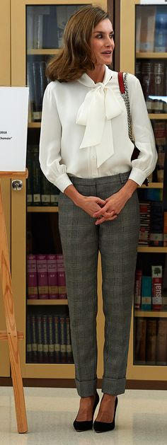 Doña Letizia wore a soft white silk blouse featuring a pussy-bow neckline, Mango 'Kennedy' Prince of Wales suit trousers, red Zara laser cut leather crossbody bag, CH Carolina Herrera pumps, TOUS cultured freshwater pearl drop earrings, and an oversized ring with green stones. Queen Letizia attends the opening of vocational training course 2017/2018 at the Segundo de Chomon Secondary School in Teruel. 27 September 2017.