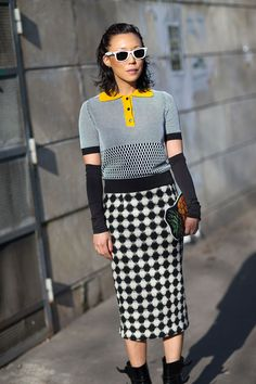Prada top with bright yellow detail, checkered  calf length skirt, ankle boots, black arm warmers. So cool! Paris Fashion Week, Street style.