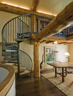 Mountain Living Home Magazine (Denver) | Cove lighting accents natural wood beams above the spiral staircase | Designer: Associates III Interior Design