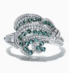 A bracelet of green tourmalines and diamonds set in platinum hugs the curves of the wrist much like the waves hug the shore.