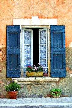Vertical window panes that open, framed by blue shutters and a widow box.