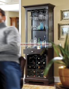 690004 Howard Miller wine cabinet furniture.The Metropolis Bar cabinet features an elegant design with a black coffee finish on select hardwoods and veneers and satin nickel hardware.This transitional cabinet features an elegant flat-top pediment and cutout base. Four glass doors provide an opportunity to display glassware, wine, and spirits.The metal wine rack in the lower cabinet offers storage capacity of 20 bottles.Black Coffee finish on select hardwoods and veneers.
