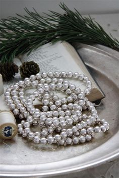 Jeanne d'Arc Livíng Blog -- I love love love pearls, and even use them mixed in with white pumpkins... Here, they are used to great effect with Christmas greenery