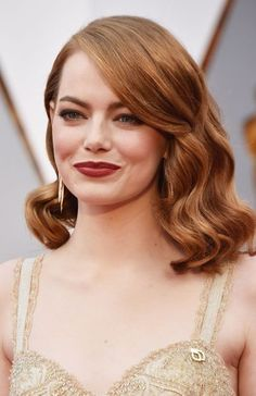 Emma Stone, who won the award for Best Actress In A Leading Role, wore her hair in side-swept Hollywood curls complemented by rose-red lipstick and shimmering eyeshadow.