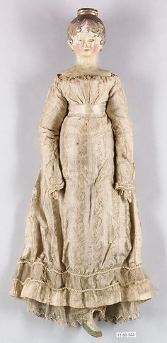 Doll, materials not listed (appears to be painted wood, gown of silk damask trimmed with silk satin ribbon, braid and net, petticoat of muslin), date not given (appears to be c. 1810-15, based on clothing and hair), American. Metropolitan Museum of Art accession no. 11.60.322