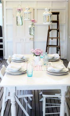 Simple French farmhouse tablescape, white, hanging lanterns, pink flowers, teal blue glass, ladder