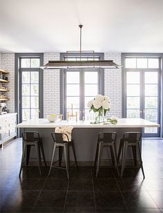 gray kitchen cabinets, white subway tile with dark grout, chevron floors, open shelving, and black accents.