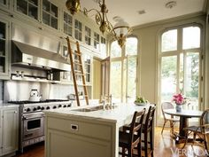 When kitchens have very tall ceilings, upper cabinets maximize the use of storage space. The rail from the Putnam Rolling Ladder Co. adds a piece of utilitarian hardware to the cabinets and gives the room a bit of sparkle. If the ceilings are not as high, a Cramer step stool works just as well instead of a kitchen ladder.