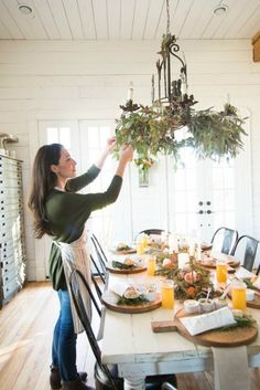joanna gaines entertains |  Tall brass candlesticks provide plenty of ambiance  and drinks are served in stylish mason jars. Each place setting is anchored by a rustic wooden bread board, and an elegant white napkin.