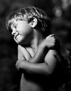 Little boy laughing and hugging himself. Perfect lighting.. genuine smile